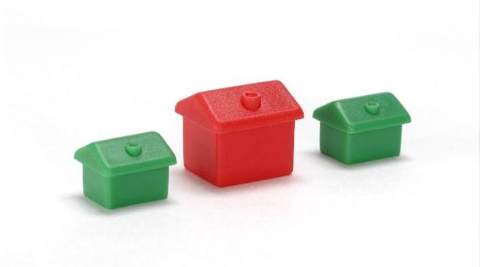 Red plastic miniature-house standing amongst green ones