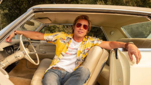 Brad Pitt's character Cliff Booth in Once Upon A Time in Hollywood. Wearing a yellow Hawaiian shirt and sunglasses in the front seat of a car.