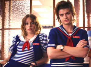 Two Scoops Ahoy employees, Steve and Robin, wearing sailor-like outfits leaning on a window sill.
