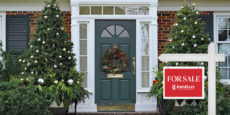 Front door of a JohnHart home for sale, flanked by two decorated Christmas trees