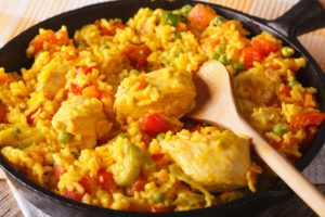 A large pan full of arroz con pollo (chicken with rice), and a spoon to serve it.