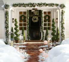 Front door to a home, covered with garland, wreaths, and Christmas decor all around, while a brick path to the door is just barely perceptible among the heavy snow