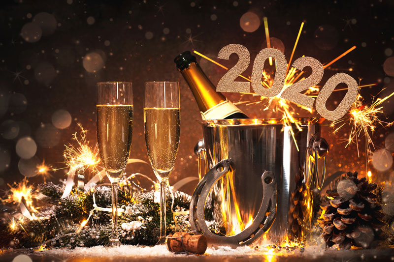 Two glasses of champagne and the bottle in an ice bucket, with 2020 numbers and sparklers