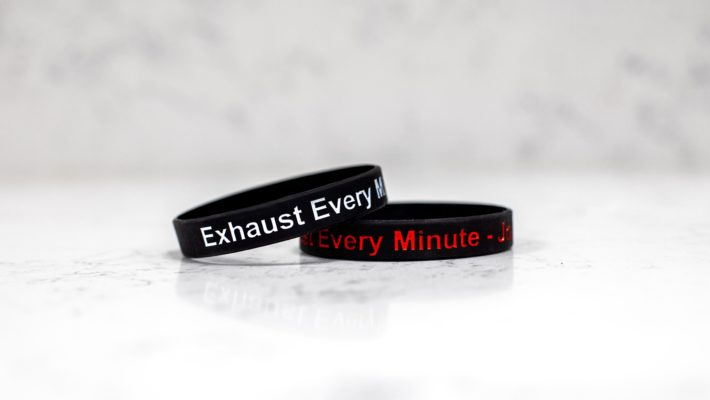 Exhaust Every Minute wristbands, one with red text, one with white text
