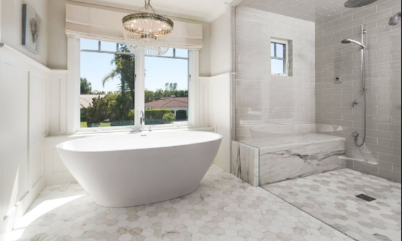 A white bathtub and modern bathroom, flooded with midday sunlight