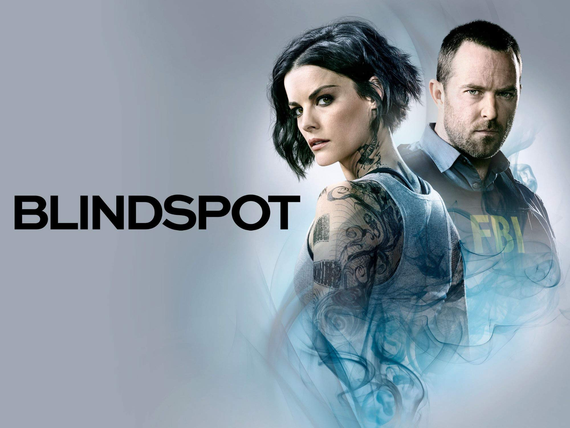 a woman and man against a light grey background and teal smoke she has tattoos and he is wearing an FBI vest blindspot