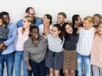 13 people diverse group with white brown and black skin standing together arms over each other's shoulders smiling laughing and acknowledging one another in front of a white background some women wearing pants or skirts men wearing pants multicolored outfits old and young people