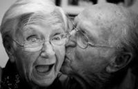 black and white photo of an old couple both wearing glasses woman's mouth is open and smiling she is happily surprised man is kissing her on the cheek he is balding they are in their house