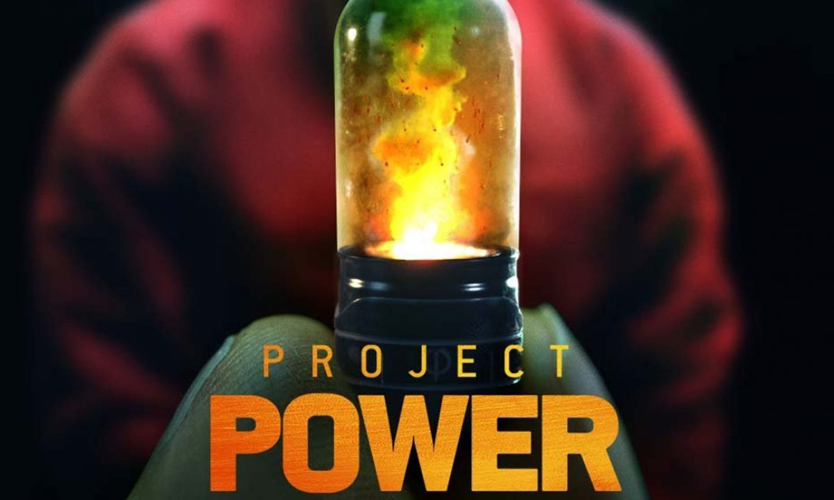 two fingers holding a glass and metal pill with power and fire inside with a blurred out man in the background wearing a red sweater black surrounding project power