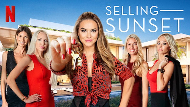 selling sunset female realtors 5 of them wearing red and black the middle one holding out gold keys in front of a house with a pool and blue sky