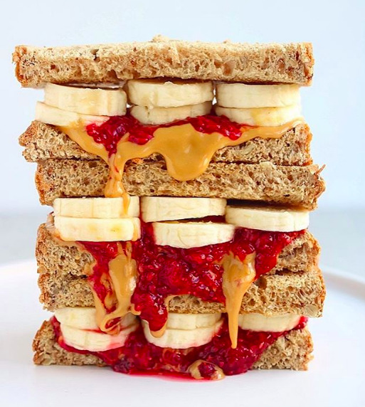pb&j banana sandwich on wheat bread triple stacked with jelly and peanut butter overflowing with white background