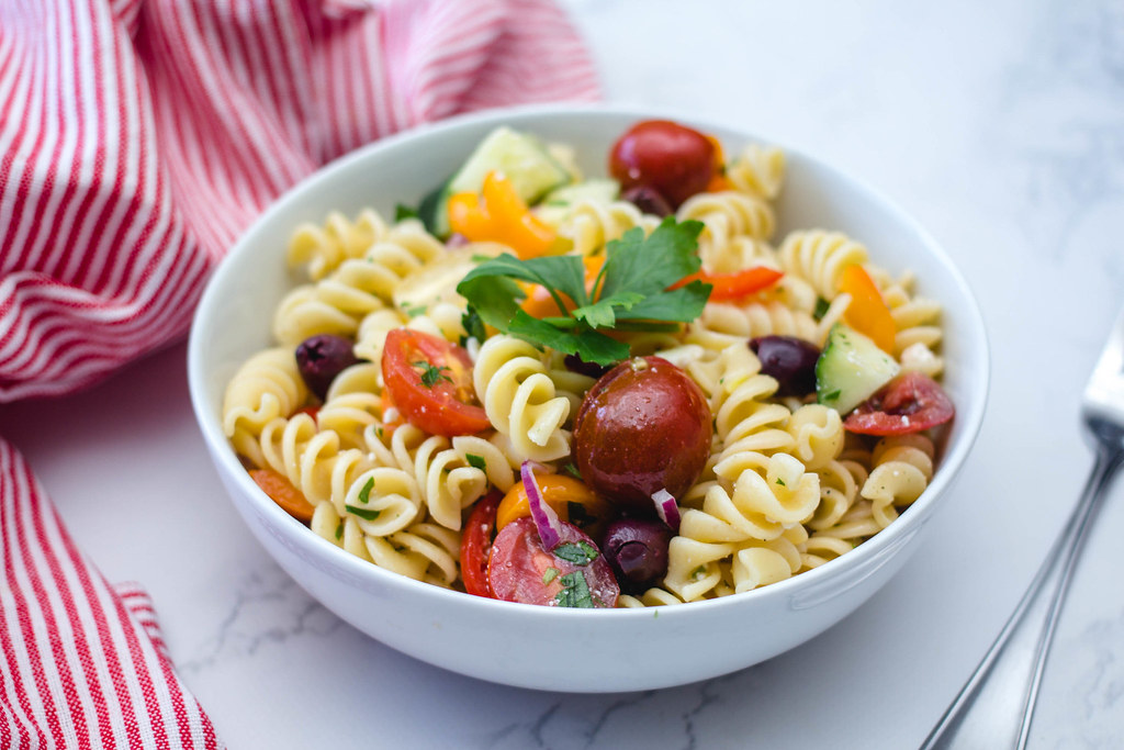 twisted pasta pasta salad with olives fruits tomatoes bell pepper cheese in a white porcelain bowl on a white and gray marble counter top with a fork on side and a red and white striped fabric napkin green parsley on top