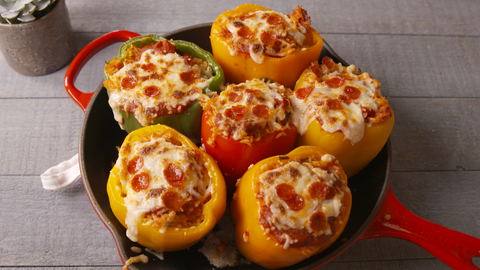 pepperoni pizza in a bell pepper half red green and yellow bell peppers on a red frying pan on grey wood table with a potted plant in background