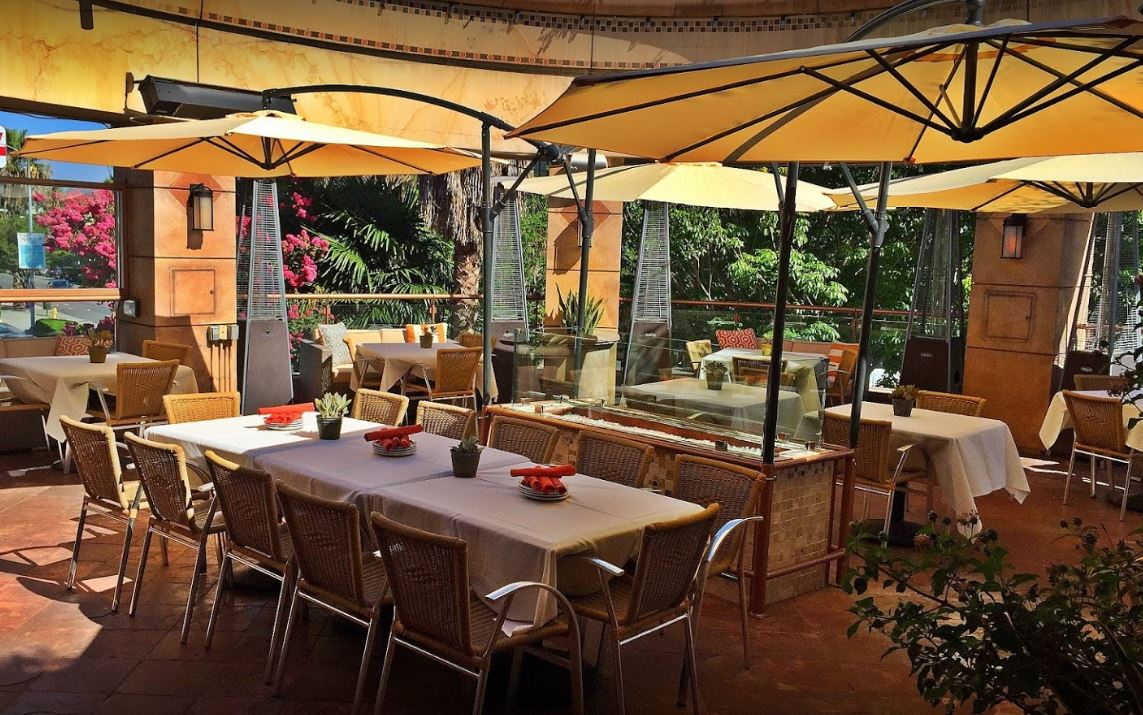 anejo cafe and grill outdoor dining with stone floor tables with white table cloths yellow paint and yellow umbrellas beige wicker chairs red folded napkins plants on tables and around heaters lights
