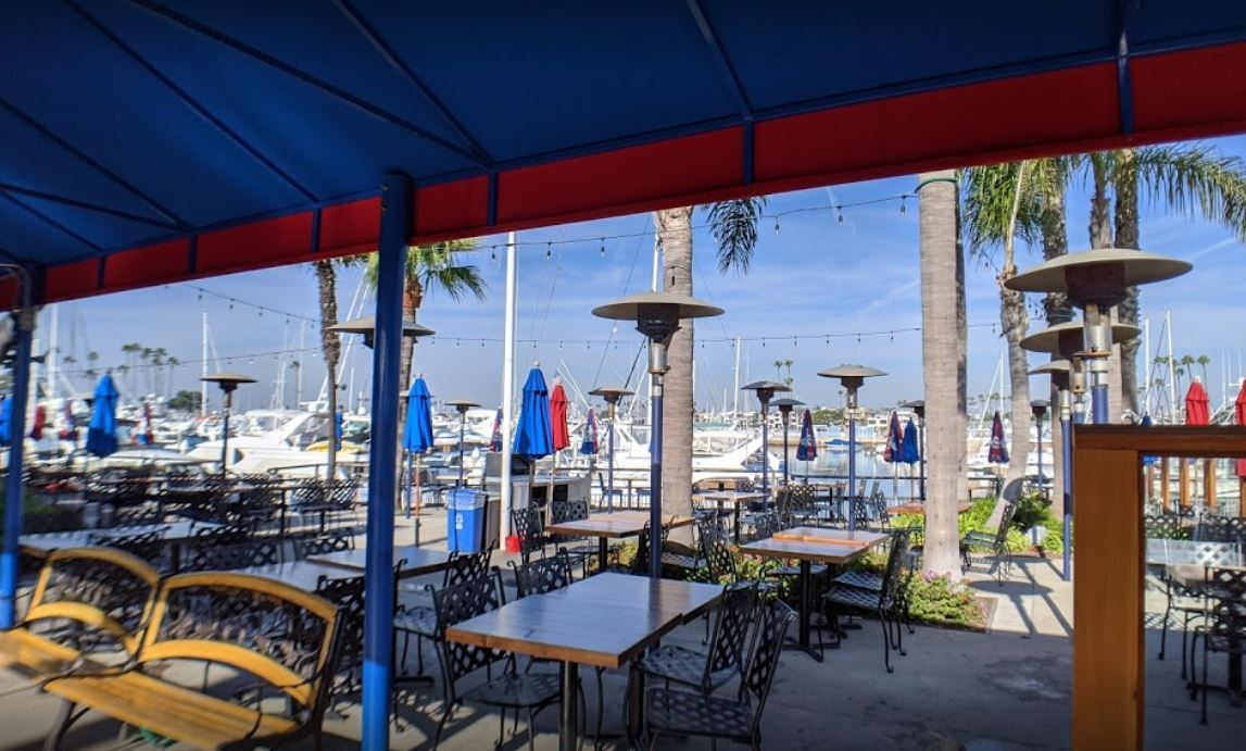 waterfront view outdoor patio boats yachts blue and red umbrellas wood and metal tables chairs and benches cement floor palm trees heat lamps blue sky