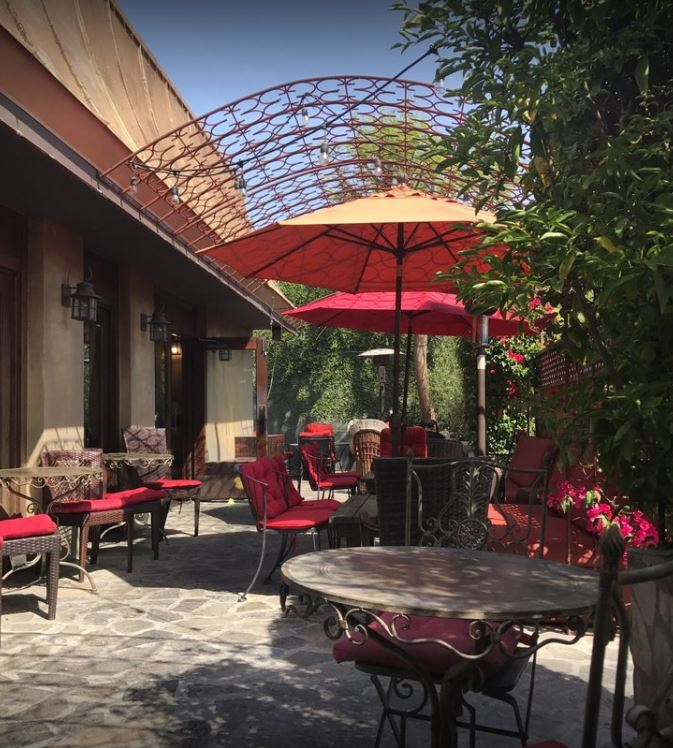 garden cafe outdoor patio with trees plants and vines surrounding on brick floor with stone tables metal chairs with red cushions enclosed with a metal pergola