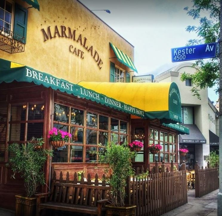 marmalade cafe breakfast lunch dinner brunch happy hour restaurant front yellow green and wood with pink hanging flowers wood gate plants upper windows with yellow and green striped shades and metal under part glass windows outdoor patio