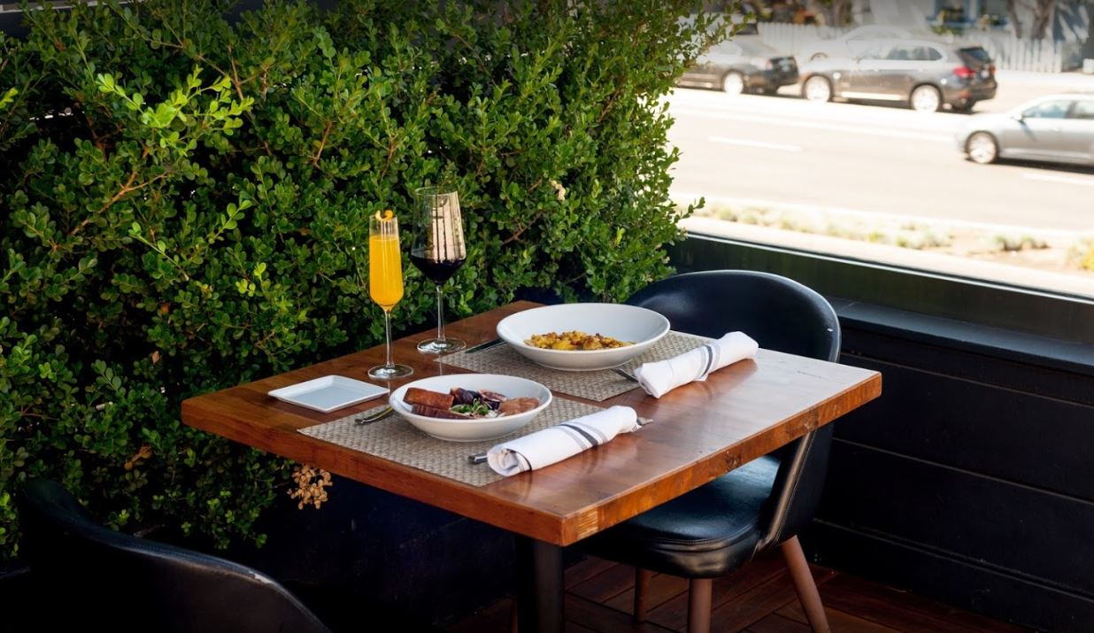 medium dark wood table with black leather chairs set with beige place mats white napkins with black stripes white plates and bowls with food mimosa and red wine street view with green bush on side