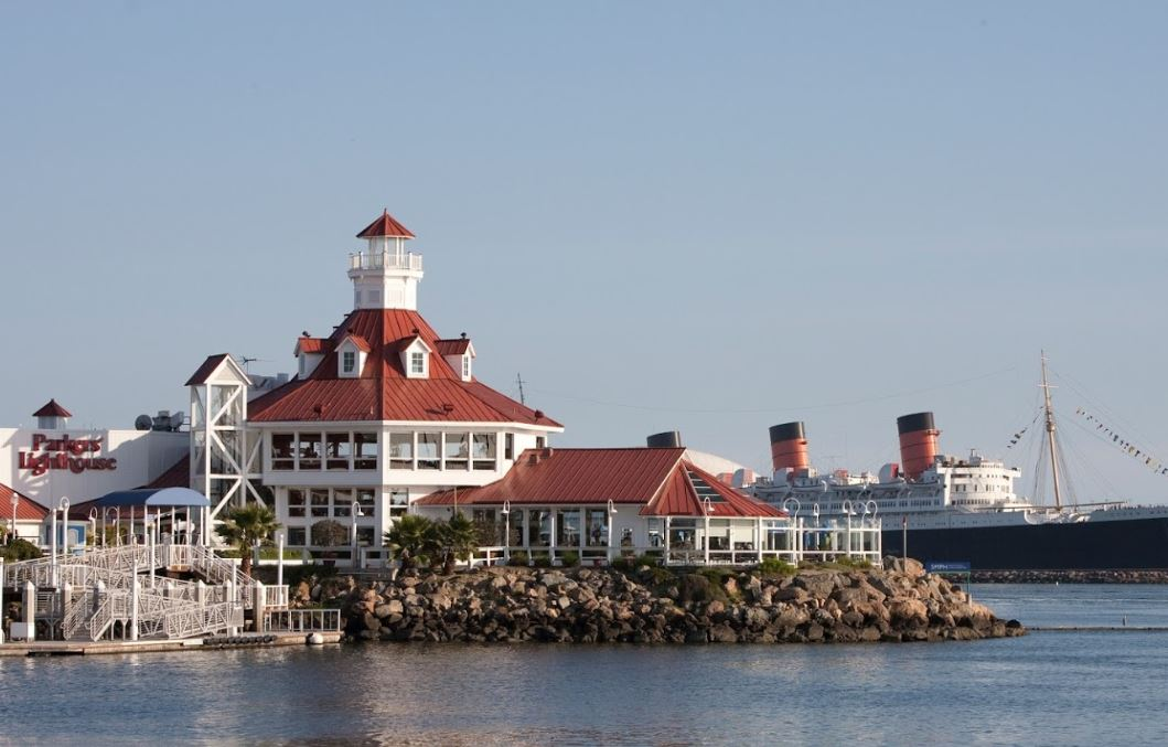 ocean sitting restaurant white metal gating queen mary behind red roof with white building rocks below watch tower