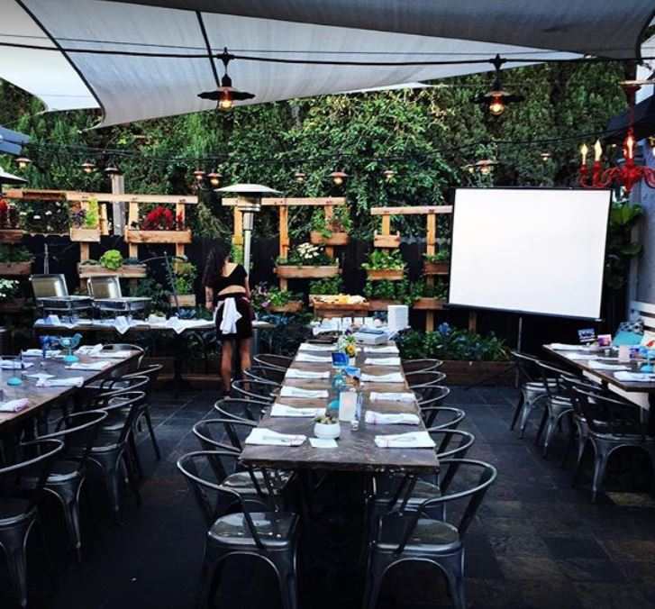 outdoor patio with long wood and metal tables and metal chairs with place setting napkins and silverware flowers and candles on table surrounded by a wall of plants heat lamps tented lighting screen chandelier and waitress in black outfit with white napkin