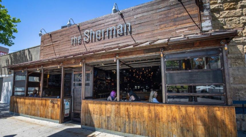 the Sherman front side of business looks like old wood but is new with wood overhang windows outdoor patio with people sitting