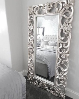 grey walls and carpet corner of bed with large standinf designed mirror with metal frame