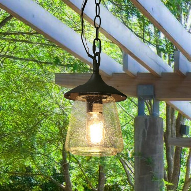 green tree branches and leaves in background with wood overhang and a black chain leading to a clear industrial light outdoor fixture