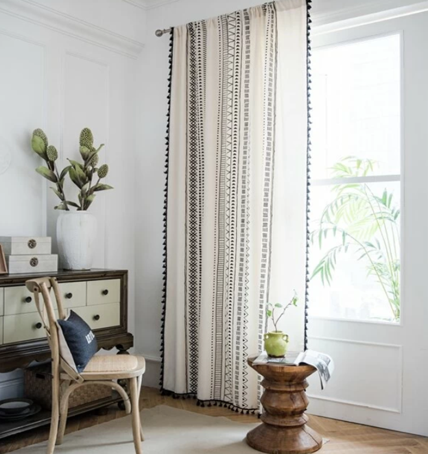 designer room with wood floor beige chair with white and navy pillow dresser with decor and a plant side wood table with green plant on top beige rug window and white and black patterned curtain