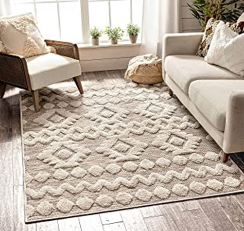 wood floor with white and beige patterned rug a beige couch beige chair white curtains with window plants