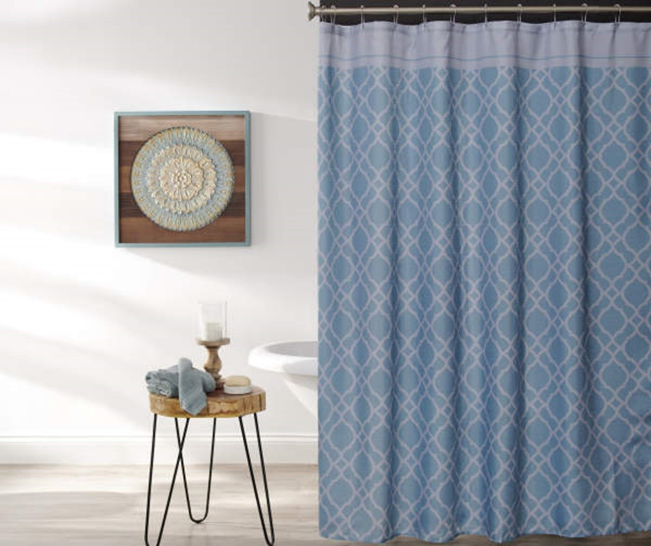white walls light floor with blue patterned shower curtain and hanging art with wood side table blue wash cloths and candle