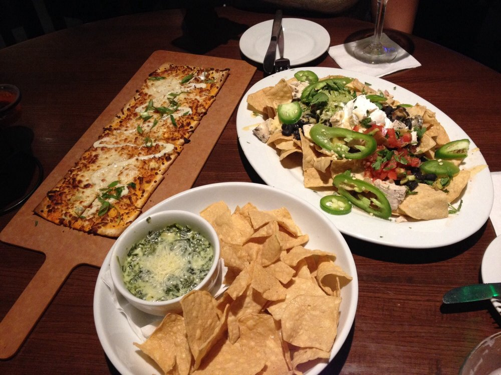 white plates with spinach artichoke dip and chips nachos with sour cream and jalapenos silverware and flatbread