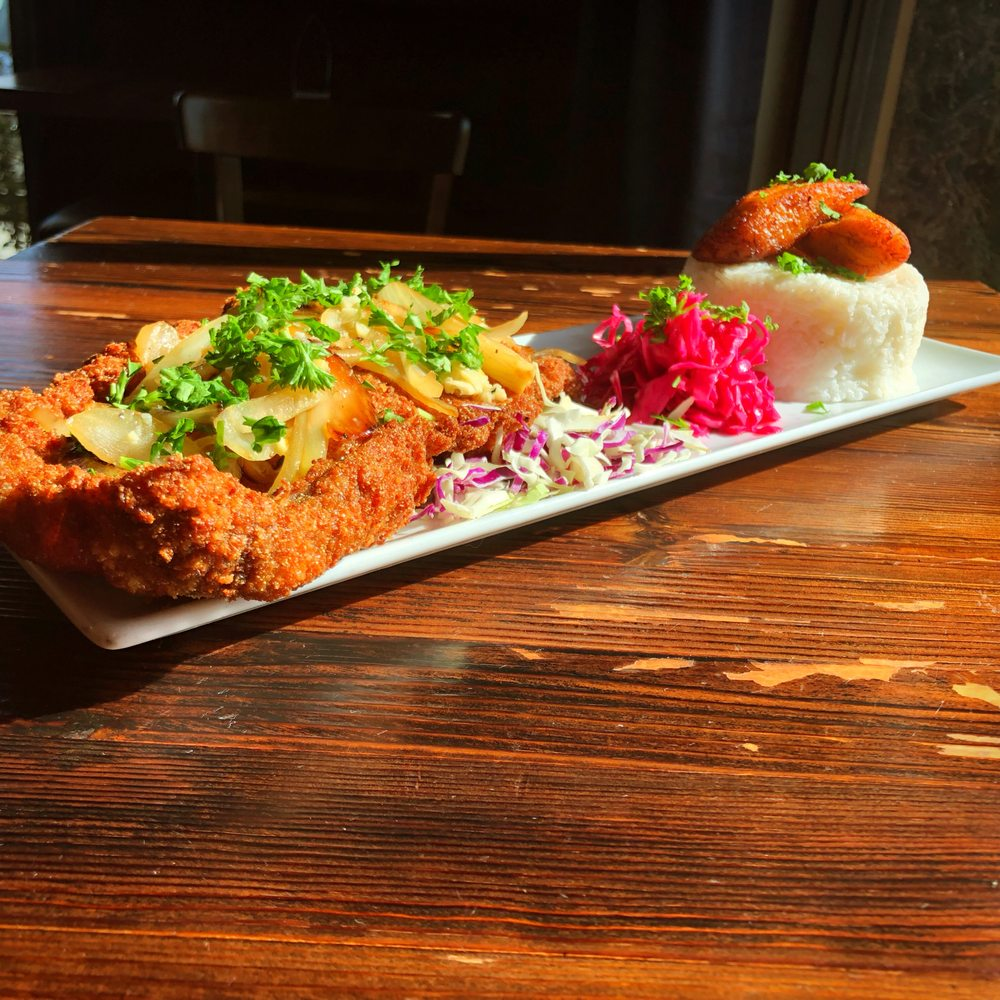 wood table with white long rectangular plate on top fried meat with toppings and cilantro coleslaw red onion and a rice cake with meat on top