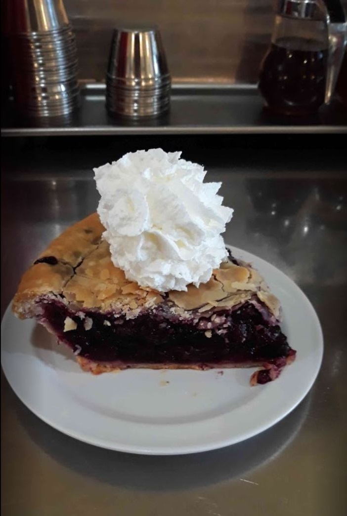 berry pie purple on a white plate with whip cream on top on a metal table