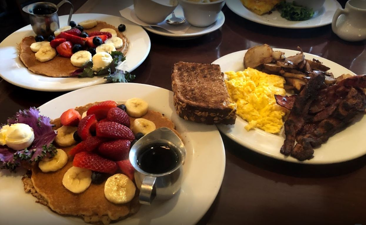 wood table with white round plates with chocolate chip pancakes and banana strawberries blueberries butter eggs toast bacon potatoes and syrup
