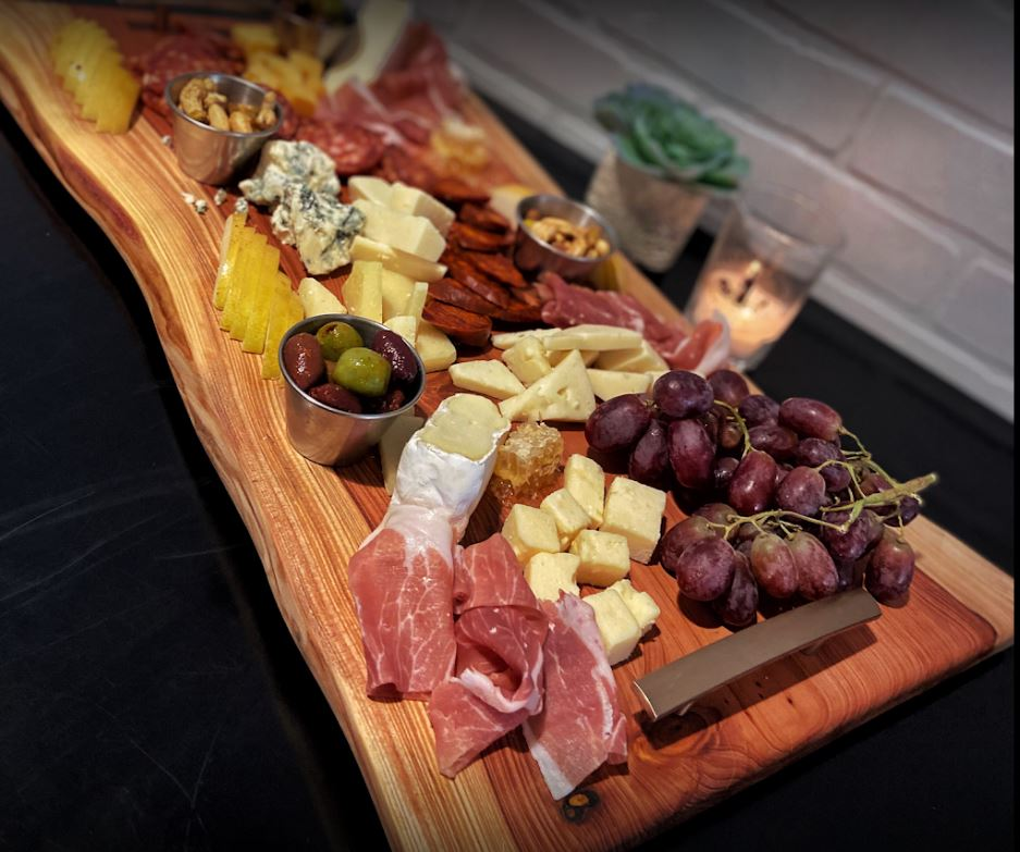 black table cloth with long wood platter of meats grapes cheeses nuts and veggies
