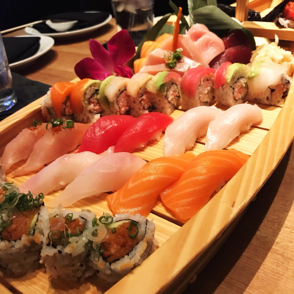 wood table with large wood boat filled with an array of sushi rolls and hand cut rolls with ginger and wasabi