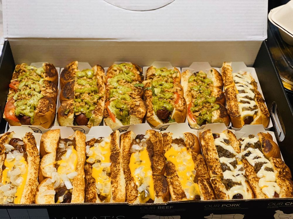 13 hot dogs with loads of toppings in a black box