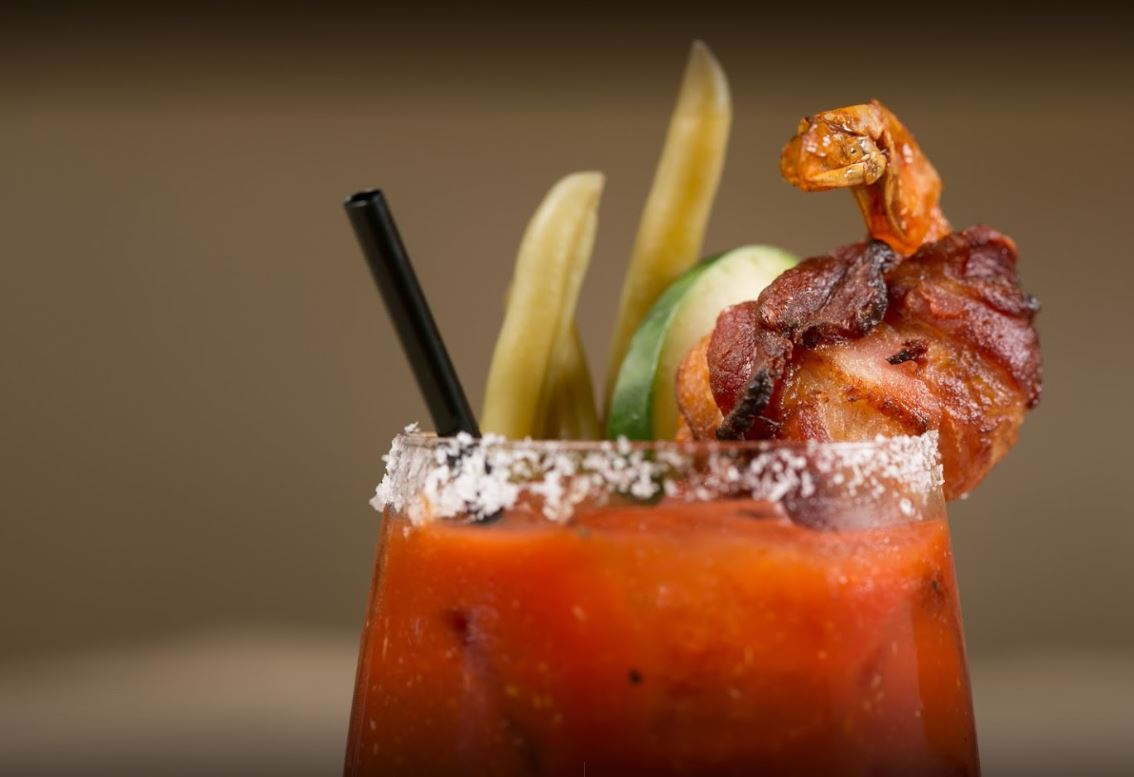 beige blurred out background with a close up shot of the top of a bloody mary with a salted rim bacon shrimp pickles and cucumber and a black straw