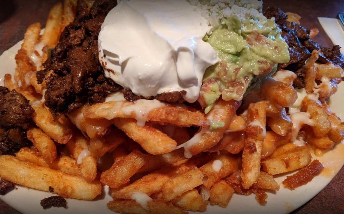 fries with chili beef guacamole sour cream and dressing on a white plate
