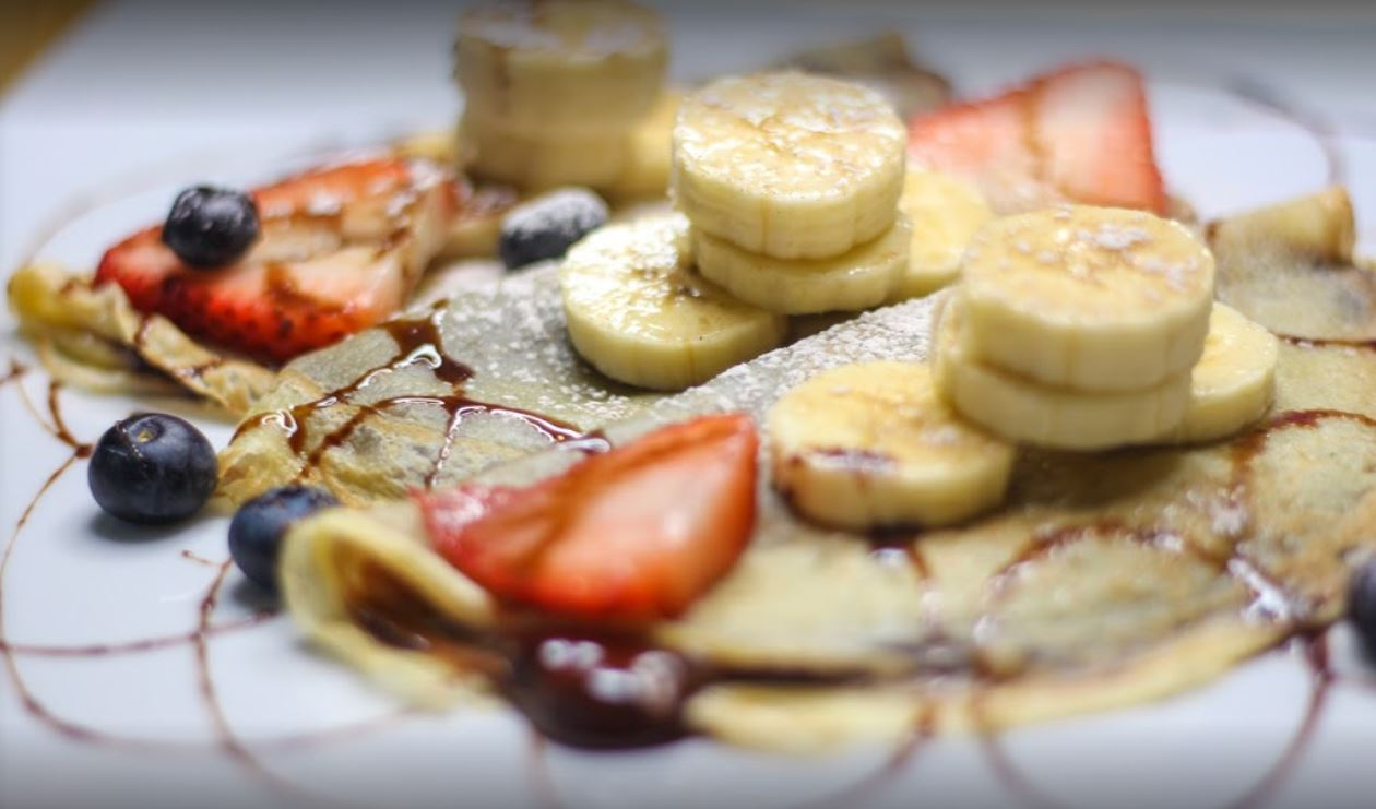 white plate with banana strawberry blueberry and nutella crepes with powdered sugar and chocolate drizzle on top
