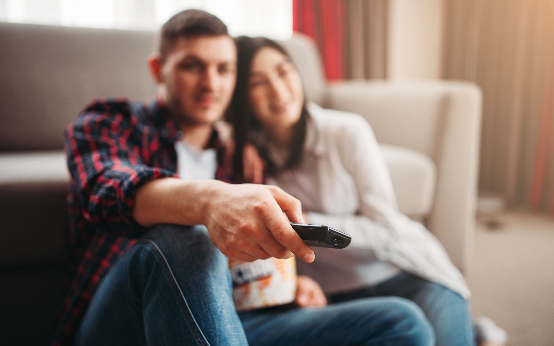 A romantic couple, man and woman, sitting down together on the floor cuddled up getting ready to watch a movie with the male holding a remote in his hand.