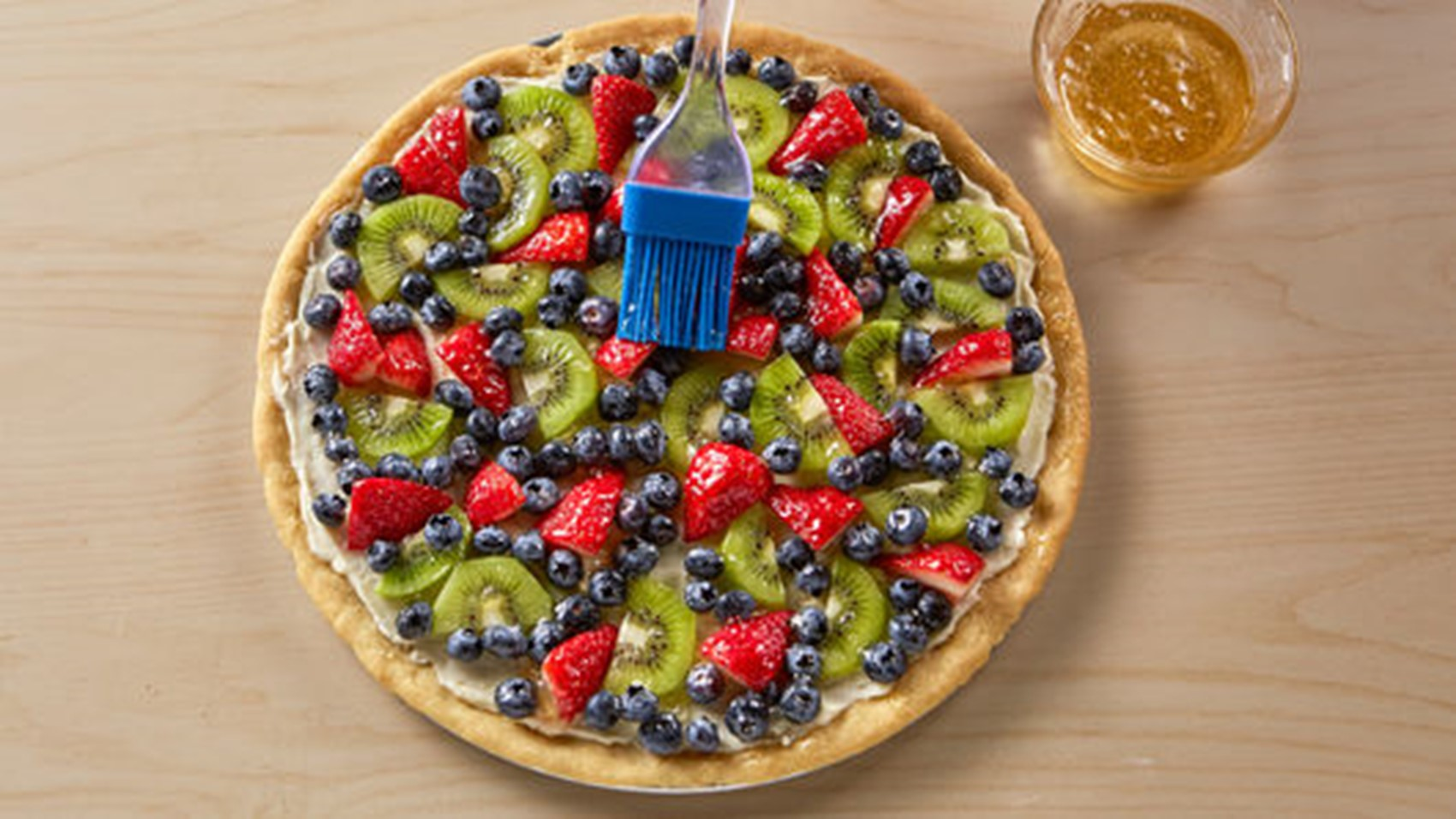 fruit pizza on wood table and glaze and glazer