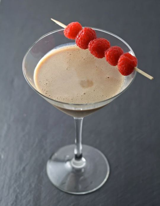 Chocolate raspberry martini Valentine's Day cocktail in a martini glass with a charcoal gray background. The milky brown chocolate martini is garnished with 5 fresh raspberries on a toothpick.