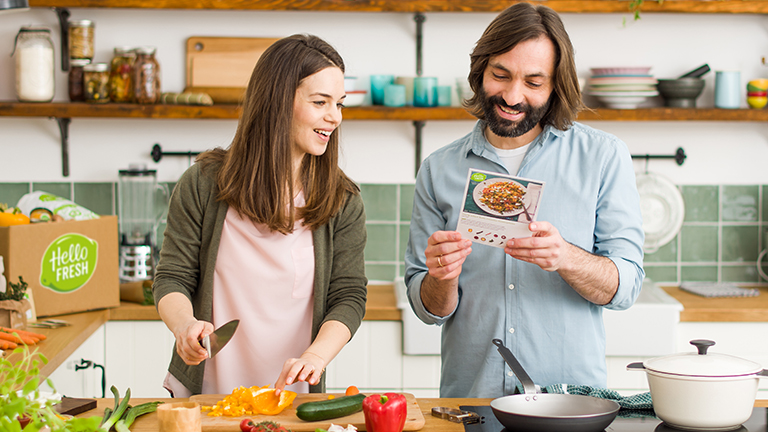 A white couple in their early 30's reading HelloFresh instructions in a bright kitchen, preparing to cook together as a part of a romantic date night.
