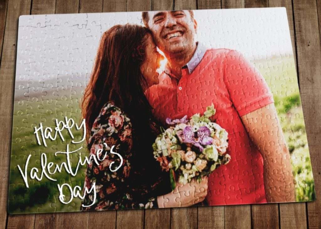 A custom-made puzzle of a happy smiling couple with the words Happy Valentine's Day in white lettering in the lower left portion of the puzzle.