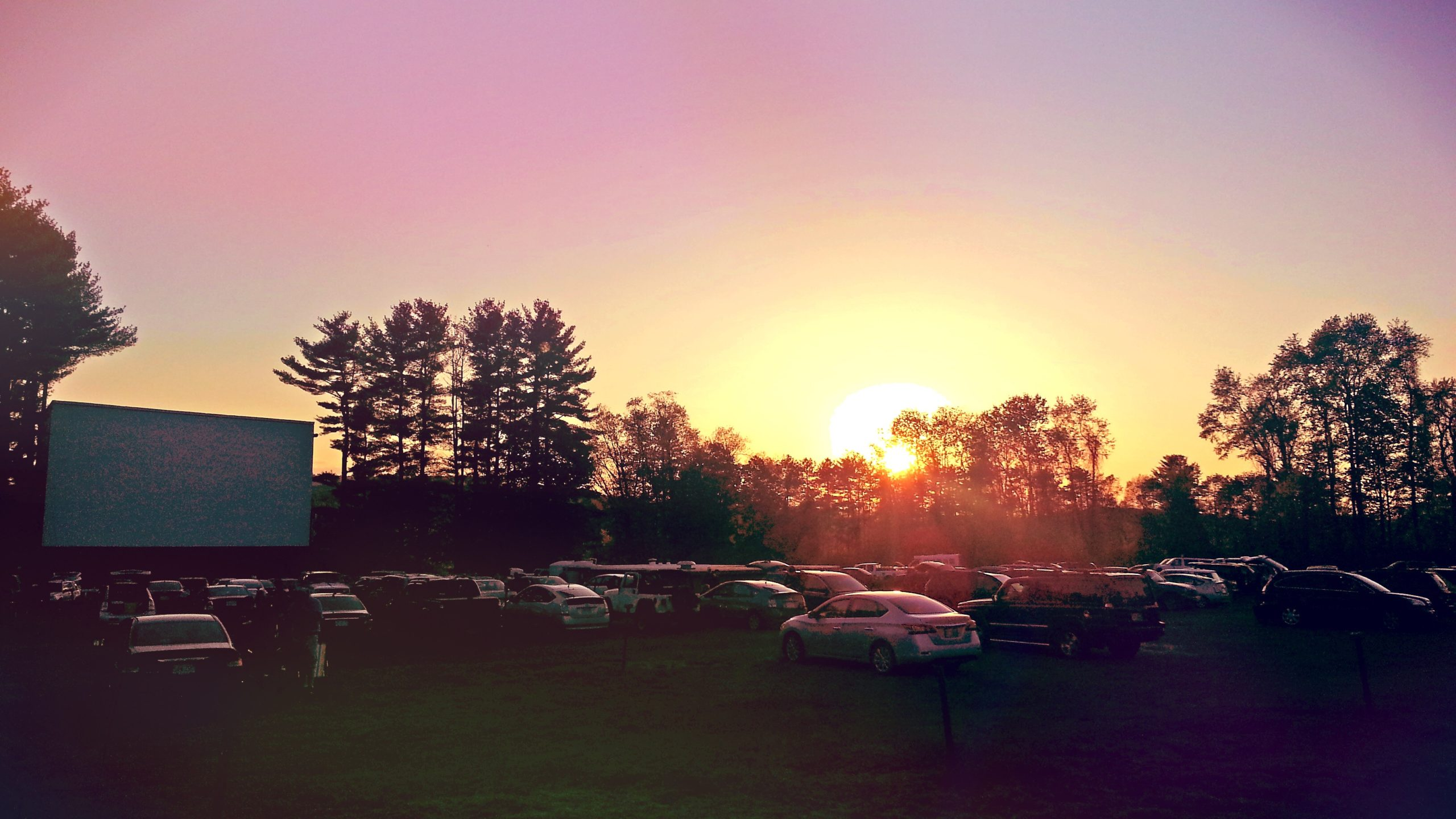 A drive-in movie theater fills up as the sun sets