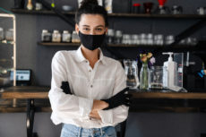 Female small business owner stands in front of her bar, wearing gloves and a face mask.