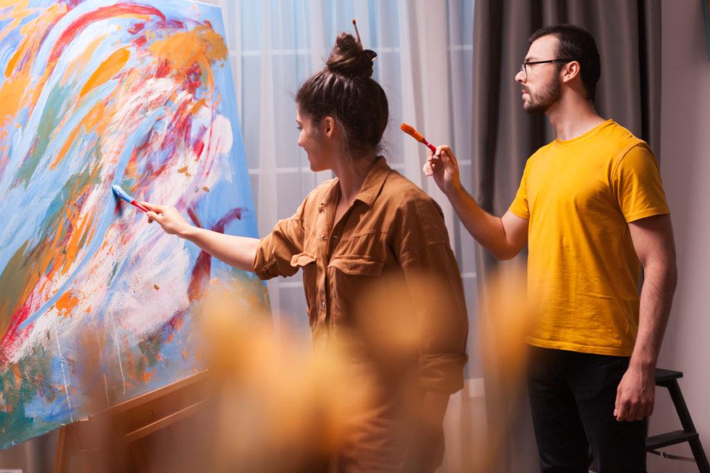 Creative couple painting on canvas in art studio. Modern artwork paint on canvas, creative, contemporary and successful fine art artist drawing masterpiece