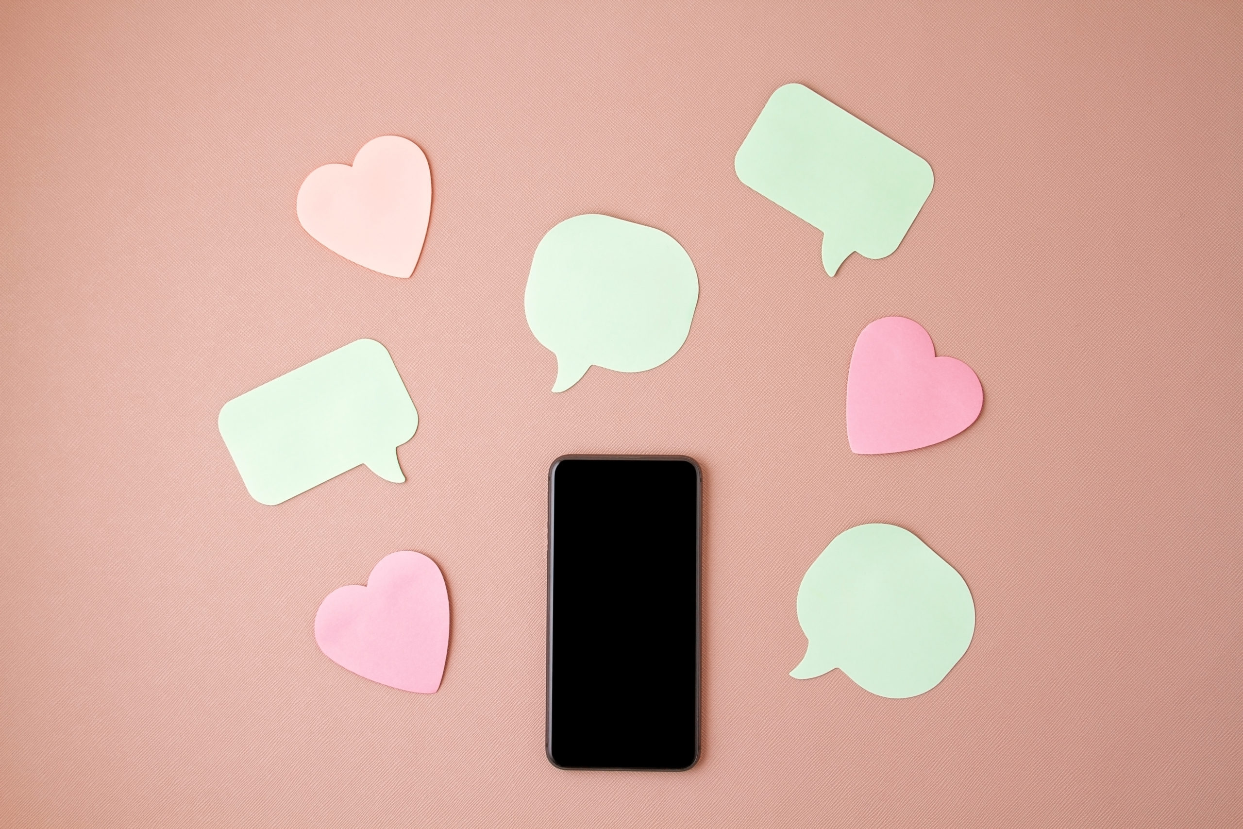 Mockup flat lay with smartphone and hearts and speech bubbles. Social networking, likes, follow, comments, share concept