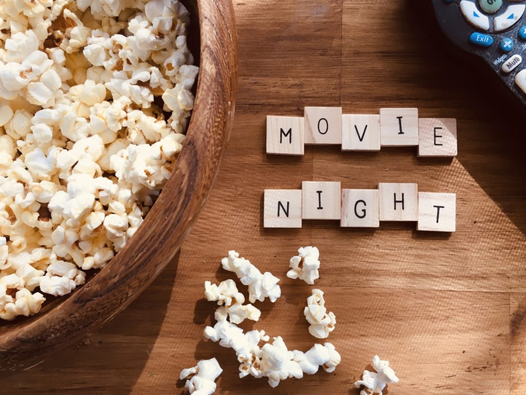 """""""Movie Night"""" spelled out via Scrabble letter pieces, paired with a wooden bowl of popcorn with kernels overflowing onto the wooden table. A TV remote in the upper-righthand corner."""